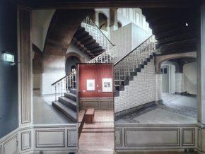 Doorkijk van zaal 8 naar zaal 9. Op de muur zi een foto van het trappenhuis